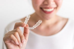 person holding an Invisalign aligner