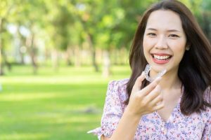 Smiling woman holds Invisalign in Ellington while travelling for summer